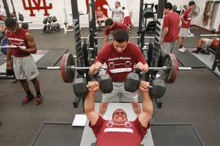 Cimarron Memorial student Gabriel Chavez spots Juan Gonzalez as he lifts weights in their new weight room Tuesday, April 22, 2014.