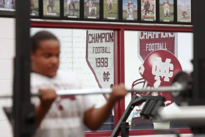 Banners from Cimarron Memorial's past football championships hang on the wall as students lift weights in their new weight room Tuesday, April 22, 2014.