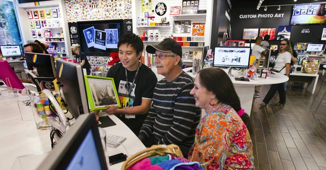 Jerome Tuason assists Roy and Karen Myers of S. Rockwood, Mich., in making Polaroids for their daughter Wednesday, April 23, 2014, at the Polaroid Fotobar.