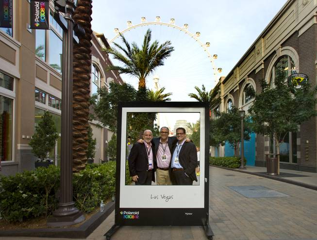 Sandy Letchner, Warren Struhl and Todd Fine stand behind by a large frame outside their Polaroid Fotobar and Polaroid Museum on Wednesday, April 23, 2014, at the Linq.