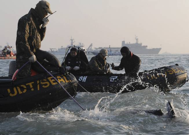 Divers look for people believed to have been trapped in the sunken ferry Sewol in the water off the southern coast near Jindo, south of Seoul, South Korea, Wednesday, April 23, 2014.