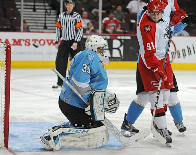 Las Vegas Wranglers center John Armstrong attempts to deflect an incoming shot into Alaska Aces goaltender Gerald Coleman during the third period of play on Wednesday night.