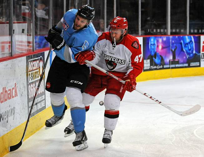 Las Vegas Wranglers forward Cody Purves (47) checks Alaska Aces defenseman James Martin into the boards behind the Aces net during the third period of play Wednesday, April 23, 2014, at Orleans Arena.
