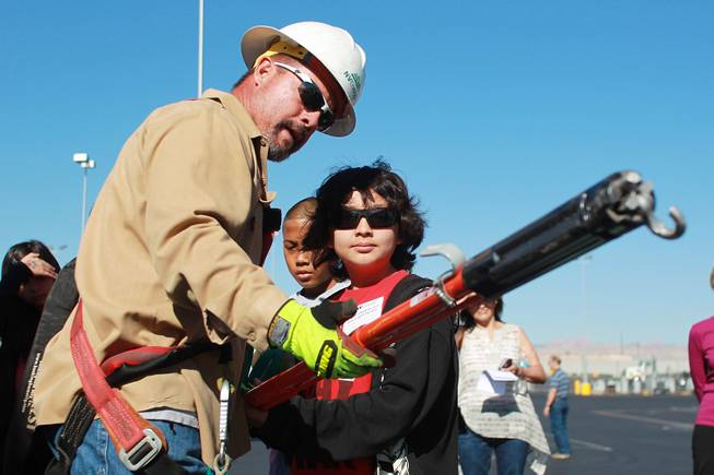 "Mark Gutierrez demonstrates the use of equipment to Gregg Parlade during ""Take Our Daughters and Sons to Work Day"" at NV Energy Thursday, April 24, 2014."