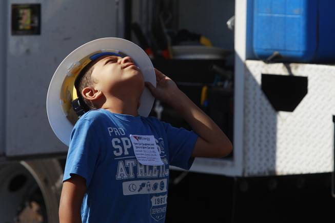 "Meki Salima watches as a line truck raises its basket during ""Take Our Daughters and Sons to Work Day"" at NV Energy Thursday, April 24, 2014."