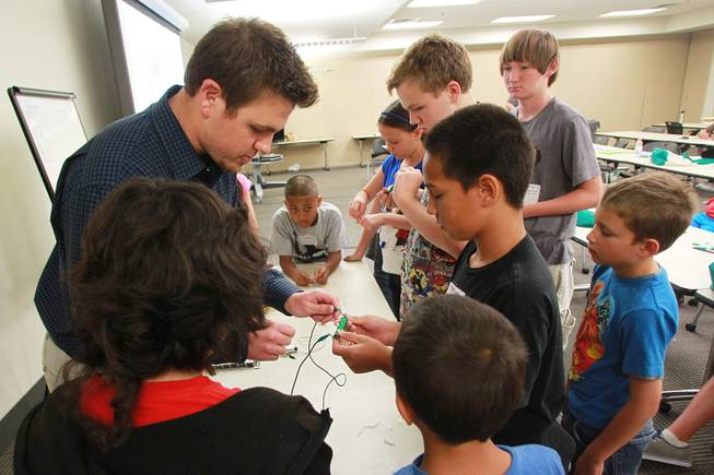 "Jake Seifman helps Tama Salima build an electromagnet during ""Take Our Daughters and Sons to Work Day"" at NV Energy Thursday, April 24, 2014."