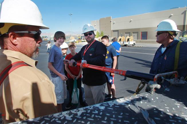 "Derek Graff demonstrates equipment to Julian Stenroos during ""Take Our Daughters and Sons to Work Day"" at NV Energy Thursday, April 24, 2014."