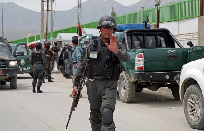 An Afghan policeman prevents journalists from approaching Cure International Hospital in Kabul, Afghanistan, Thursday, April 24, 2014. The U.S. embassy in Afghanistan says three American doctors have been killed at by an Afghan security guard who opened fire at a hospital in Kabul.