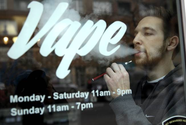 Eric Scheman demonstrates an e-cigarette at Vape store in Chicago, Wednesday, April 23, 2014. The federal government wants to ban sales of electronic cigarettes to minors and require approval for new products and health warning labels under regulations being proposed by the Food and Drug Administration.