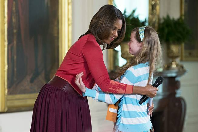 "Michelle Obama hugs Charlotte Bell, 10, after she handed the first lady her dad's resume during the White House's annual ""Take Our Daughters and Sons to Work Day,"" Thursday, April 24, 2014, in the East Room of the White House in Washington."