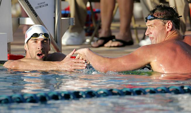 Michael Phelps congratulates Ryan Lochte on Lochte's win in the 100-meter butterfly final during the Arena Grand Prix on Thursday, April 24, 2014, in Mesa, Ariz.