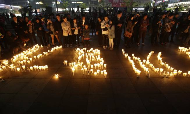 People stand near candles during a vigil for the safe return of passengers of the sunken ferry Sewol in Ansan, South Korea, Thursday, April 24, 2014.