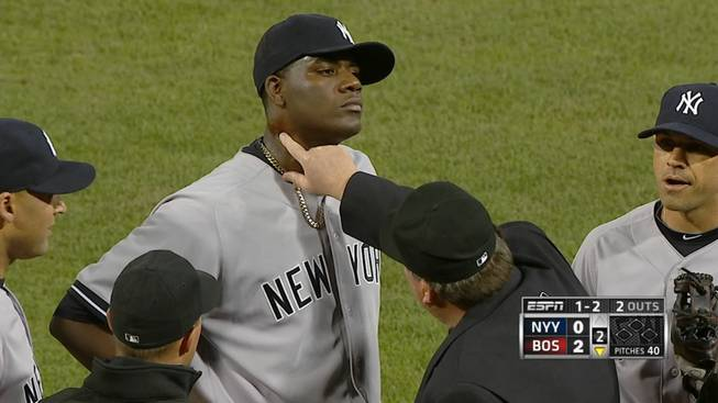 In this April 23, 2014, photo taken from video and provided by ESPN, home plate umpire Gerry Davis touches the neck of New York Yankees starting pitcher Michael Pineda in the second inning of the Yankees' baseball game against the Boston Red Sox at Fenway Park in Boston. Pineda was ejected after umpires found a foreign substance on his neck.