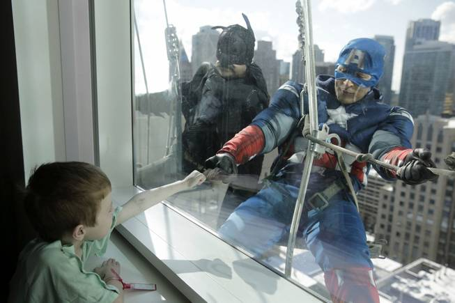 Window washers Pedro Castro, 45, as Batman, and Roberto Duran, 32, as Captain America, right, entertain patient Zakk Carrier, 5, as they hang from rope lines from the roof of the Ann & Robert H. Lurie Children's Hospital in what has become a beloved semi-annual tradition, Tuesday, April 15, 2014, in Chicago.
