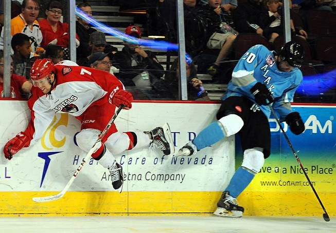 Wranglers forward Chris Kushneriuk (7) is checked against the boards by Alaska Aces defenseman Corey Syvret during the second period of an ECHL playoff game on Friday night at the Orleans Arena.