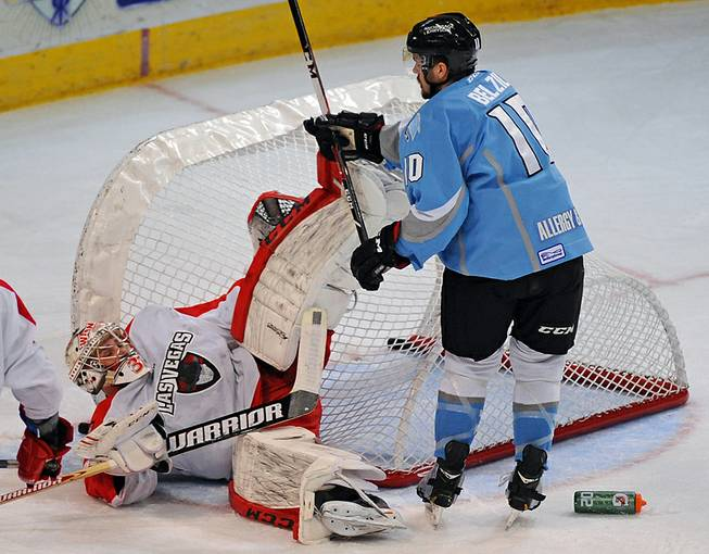 Wranglers goaltender Travis Fullerton is knocked to the ice by Alaskas Aces winger Alex Belzile during the first period of play on Friday night at the Orleans Arena.