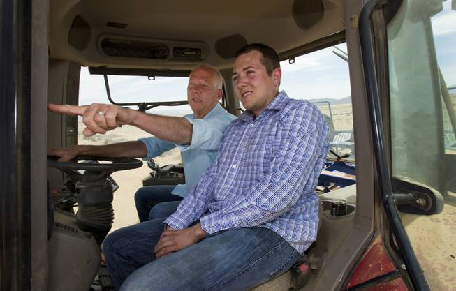 Jim Rhodes and his son Mike talk about a new field from the cab of one of their many tractors on their new Kingman Farms outside Kingman, Ariz., on Wednesday, April 9, 2014.