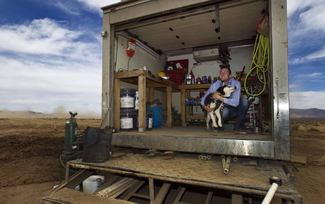 Mike Rhodes stops to play with his dog as he checks on a water-drilling rig at his father Jim's new Kingman Farms outside Kingman, Ariz., on Wednesday, April 9, 2014.