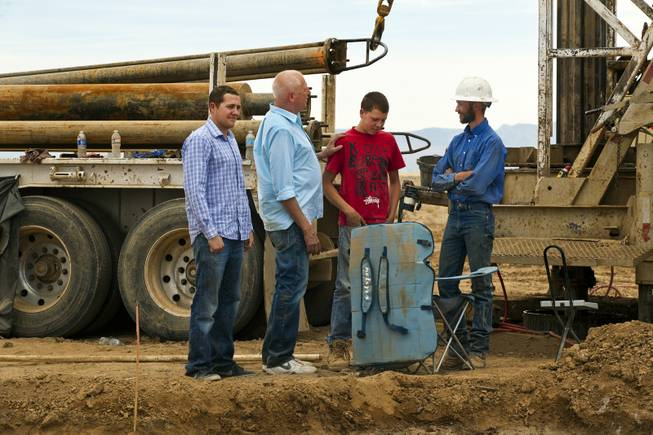 Mike, Jim and Rocky Rhodes talk with a water-drilling rig operator at their new Kingman Farms outside Kingman, Ariz., on Wednesday, April 9, 2014.