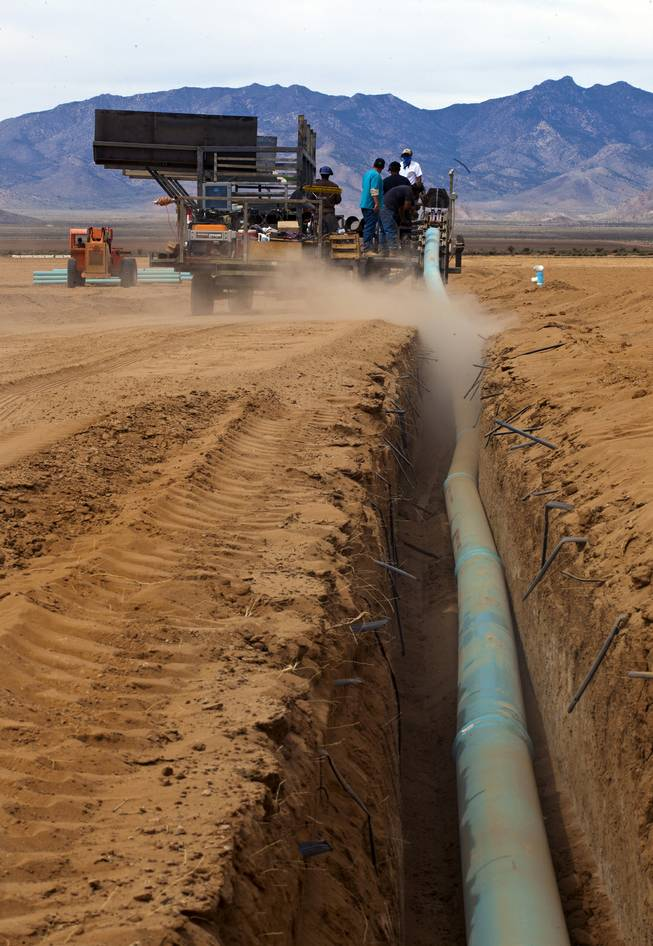 A crew works to lay more water pipe at the new Kingman Farms owned by Las Vegas developer Jim Rhodes outside Kingman, Ariz., on Wednesday, April 9, 2014.  The PipeMaster machine is an invention by Rhodes,which he says saves time, labor and makes the process safer.