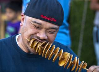 Almer Fagaragan of Las Vegas dives into a tornado potato during the Third Annual Las Vegas Foodie Fest across from the Luxor Hotel on Thursday, April 24, 2014.