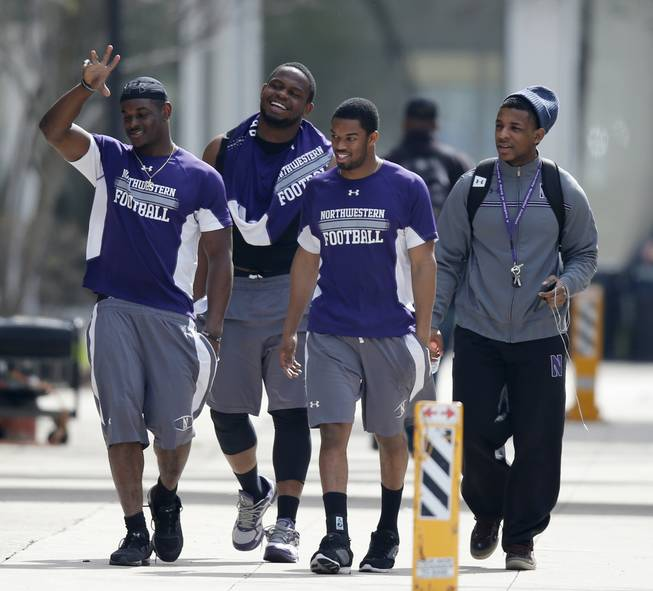 Unidentified Northwestern football players walk between their locker room and McGaw Hall, where voting is taking place on the student athlete union question Friday, April 25, 2014, in Evanston, Ill.