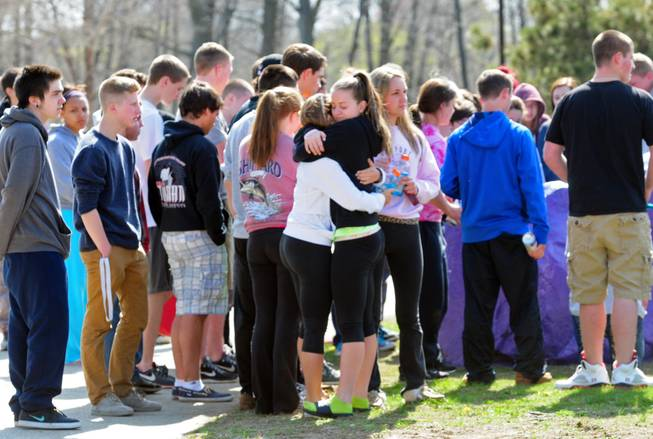 Students hug and spray paint a rock purple outside Jonathan Law High School in Milford, Conn., Friday, April 25, 2014, in memory of 16-year-old stabbing victim Maren Sanchez. Sanchez was stabbed to death earlier in the day during an altercation inside the school.