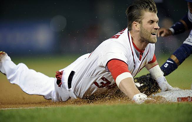 Washington Nationals left fielder Bryce Harper slides into third with a three-RBI triple during the third inning of a baseball game against the San Diego Padres, Friday, April 25, 2014, in Washington.