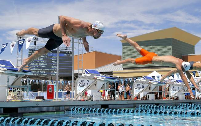 Michael Phelps leaps at the start of a 50-meter freestyle preliminary heat during the Arena Grand Prix swim event, Friday, April 25, 2014, in Mesa, Ariz.