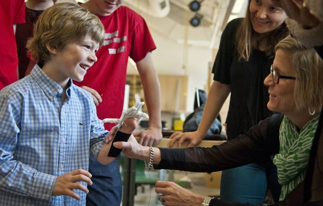 Eight-year-old Steele Songle, left, smiles at his mother Ellen after trying on an artificial hand designed by engineering students at Westtown High School, April 18, 2014, in West Chester, Pa.