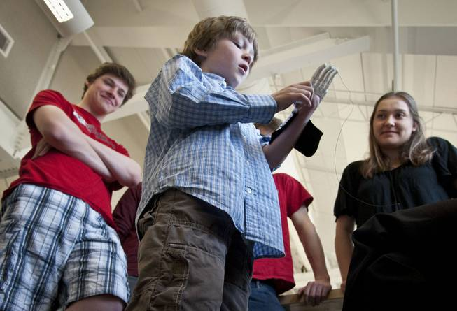 Eight-year-old Steele Songle tries on an artificial hand designed by engineering students at Westtown High School, April 18, 2014, in West Chester, Pa. In the background are engineering students Annika Cole and Alex Hunes, who helped with the design.