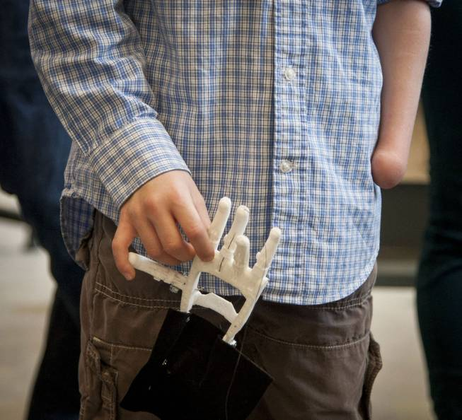 Eight-year-old Steele Songle, who was born without his left hand, holds an artificial hand designed for him by engineering students at Westtown High School, April 18, 2014, in West Chester, Pa.