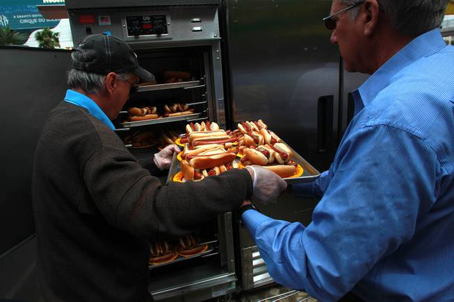 Dogs and buns are loaded into a holding container during qualifying for Nathan's Famous Fourth of July Hot Dog Eating Contest Saturday, April 26, 2014 at New York New York.