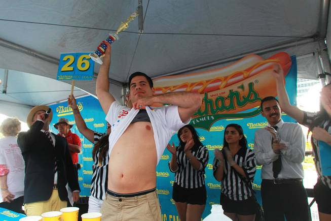 Pablo Martinez displays his stomach and trophy after winning the qualifying round for Nathan's Famous Fourth of July Hot Dog Eating Contest Saturday, April 26, 2014 at New York New York.