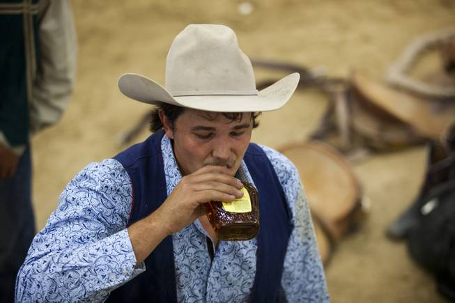 Fresno saddle bronc rider John Giacone takes a sip of Crown Royal for courage during the West Coast Regional Finals Rodeo at South Point Arena  on Friday, April 25, 2014.