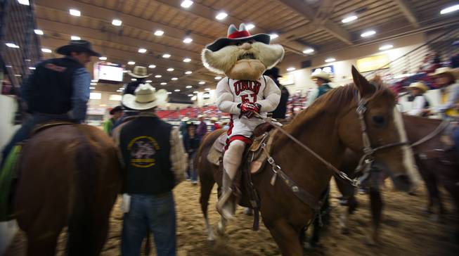 UNLV rodeo competitor Tyler Baeza portrays mascot Hey Reb during the start of the West Coast Regional Finals Rodeo at South Point Arena on Friday, April 25, 2014.