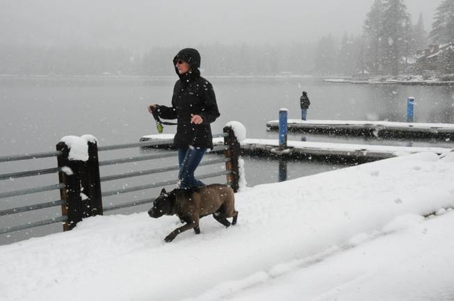 Shelley Long and her dog Brew enjoy a lakefront walk near their home as snow falls Friday, April 25, 2014, at Donner Lake in Truckee, Calif. A late-season storm brought several inches of snow to the Sierra Nevada, making for a pretty day but snarling traffic on nearby Interstate 80. In the background, a fisherman tries his luck.