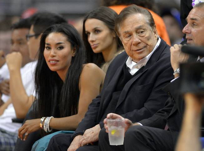 In this photo taken Friday, Oct. 25, 2013, Los Angeles Clippers owner Donald Sterling, right, and V. Stiviano, left, watch the Clippers play the Sacramento Kings. The NBA is investigating a report of an audio recording in which a man purported to be Sterling makes racist remarks while speaking to Stiviano.