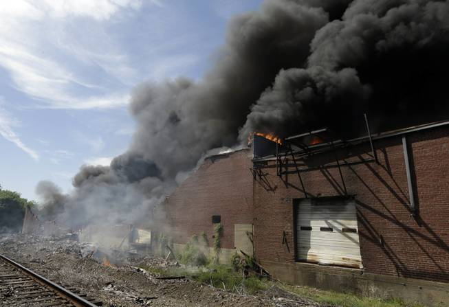 A commercial building burns near downtown Memphis, Tenn., on Saturday, April 26, 2014. Officials say four Memphis firefighters were rescued from the burning building after a wall collapsed on them.