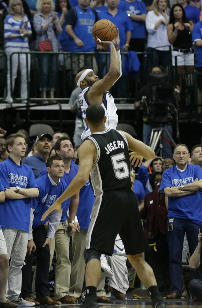 Dallas Mavericks guard Vince Carter, top, shoots the game-winning 3-point basket at the buzzer over San Antonio Spurs guard Cory Joseph (5) in the fourth quarter of Game 3 in the first round of the NBA basketball playoffs in Dallas, Saturday, April 26, 2014. The Mavericks won 109-108.