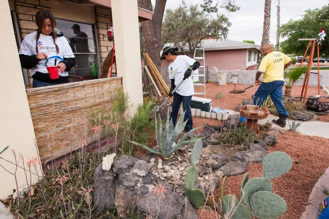Volunteers work on the desert landscaping in the front yard of the home of photographer Robert Scott Hooper and wife Theresa Hooper as part of the Rebuilding Together Southern Nevada's annual neighborhood rebuilding event in Las Vegas Saturday, April 26, 2014.