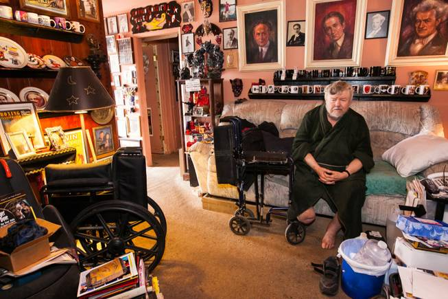 Former magician Gary Darwin, who lost his leg to diabetes, sits in his home filled with magician collectibles and memorabilia while volunteers repair the exterior of his home in downtown Las Vegas during an Rebuilding Together Southern Nevada's annual neighborhood rebuilding event in Las Vegas Saturday, April 26, 2014.