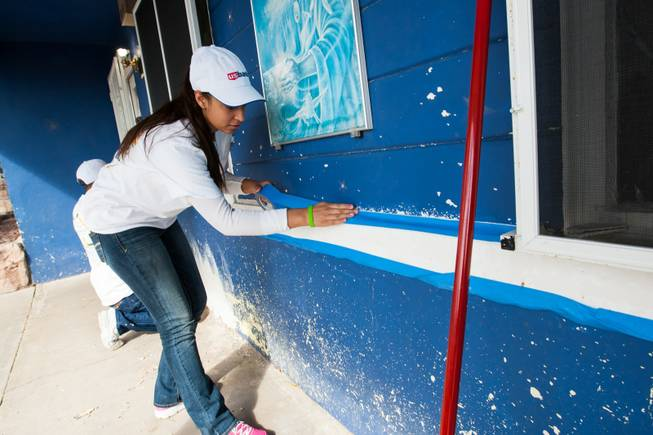 Volunteer Clarissa Tovar and Sam Berninger, left, tape windows in preparation for painting the home of former magician Gary Darwin, who lost his leg to diabetes, as part of the Rebuilding Together Southern Nevada's annual neighborhood rebuilding event in Las Vegas Saturday, April 26, 2014.