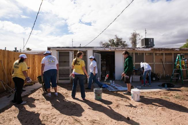 Volunteers work in the backyard of the home of former magician Gary Darwin, who lost his leg to diabetes, as part of the Rebuilding Together Southern Nevada's annual neighborhood rebuilding event in Las Vegas Saturday, April 26, 2014.
