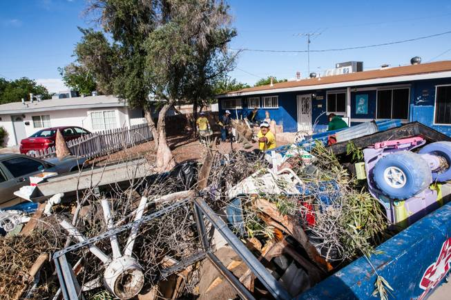 Volunteer Javier Echavarria tosses front yard debris into a dumpster of items removed from the home of former magician Gary Darwin, who lost his leg to diabetes, as part of the Rebuilding Together Southern Nevada's annual neighborhood rebuilding event in Las Vegas Saturday, April 26, 2014.
