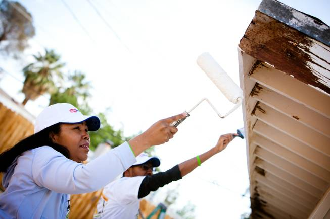 Volunteer Dionne Watson and her son, Daniel, paint the eaves of the home of former magician Gary Darwin, who lost his leg to diabetes, as part of the Rebuilding Together Southern Nevada's annual neighborhood rebuilding event in Las Vegas Saturday, April 26, 2014.