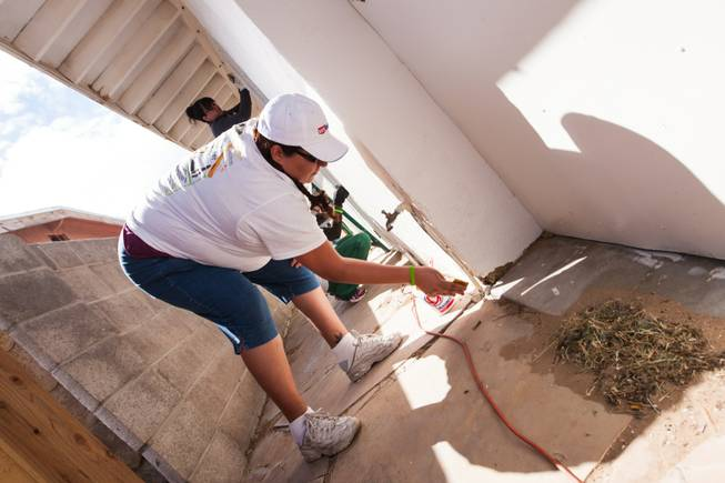 Volunteer Esperanza Meisner sands a water spigot on the side of the home of former magician Gary Darwin, who lost his leg to diabetes, as part of the Rebuilding Together Southern Nevada's annual neighborhood rebuilding event in Las Vegas Saturday, April 26, 2014.