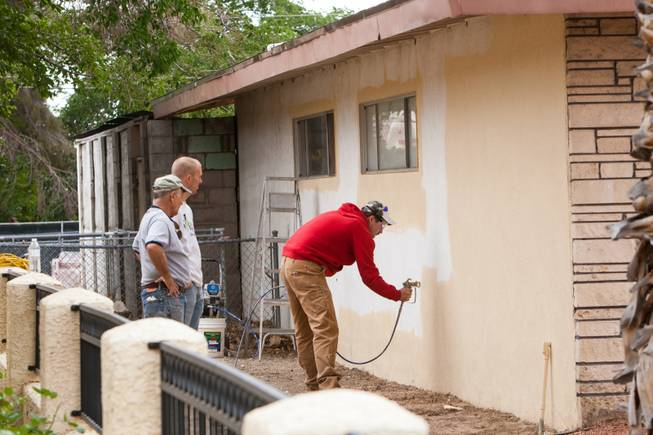 Joined by other volunteers, Daniel Strackbein spray paints along the stucco walls of the home of photographer Robert Scott Hooper and wife Theresa Hooper as part of the Rebuilding Together Southern Nevada's annual neighborhood rebuilding event in Las Vegas Saturday, April 26, 2014.