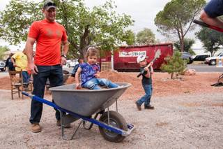 Jeremiah Blower prepares to move rocks while volunteering with his 19-month-old daughter, Beverly, and 4-year-old son, Everett, at the home of photographer Robert Scott Hooper and wife Theresa Hooper as part of the Rebuilding Together Southern Nevada's annual neighborhood rebuilding event in Las Vegas Saturday, April 26, 2014.