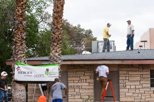 Volunteers inspect the roof of the home of photographer Robert Scott Hooper and wife Theresa Hooper as part of the Rebuilding Together Southern Nevada's annual neighborhood rebuilding event in Las Vegas Saturday, April 26, 2014.